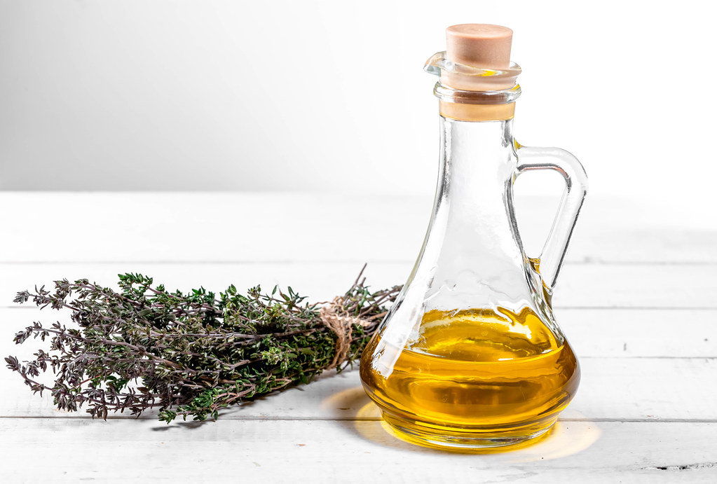 Fresh thyme with olive oil on white wooden table