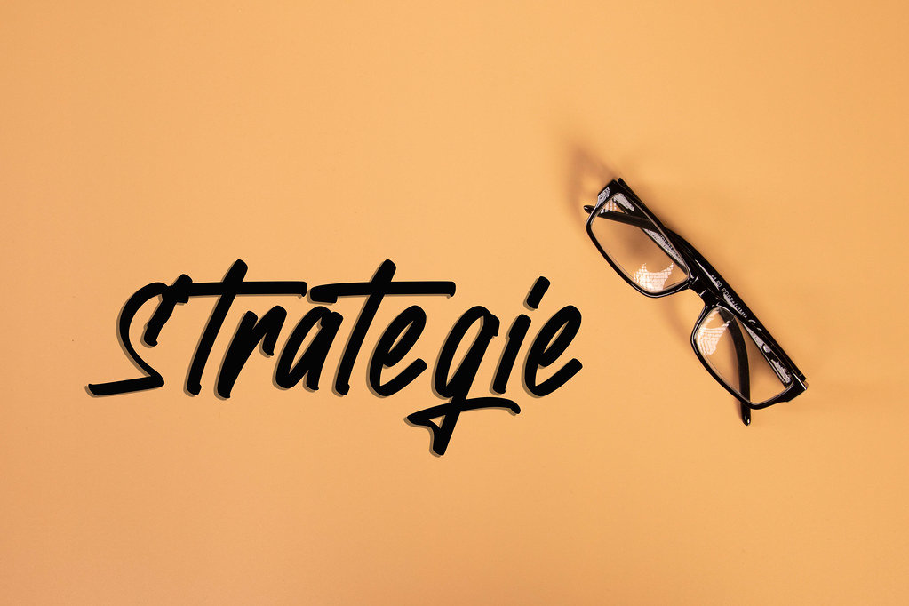 Glasses with Strategie text on orange background