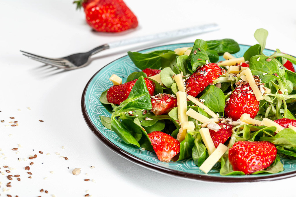 Salad with fresh strawberries, cheese and a mix of seeds