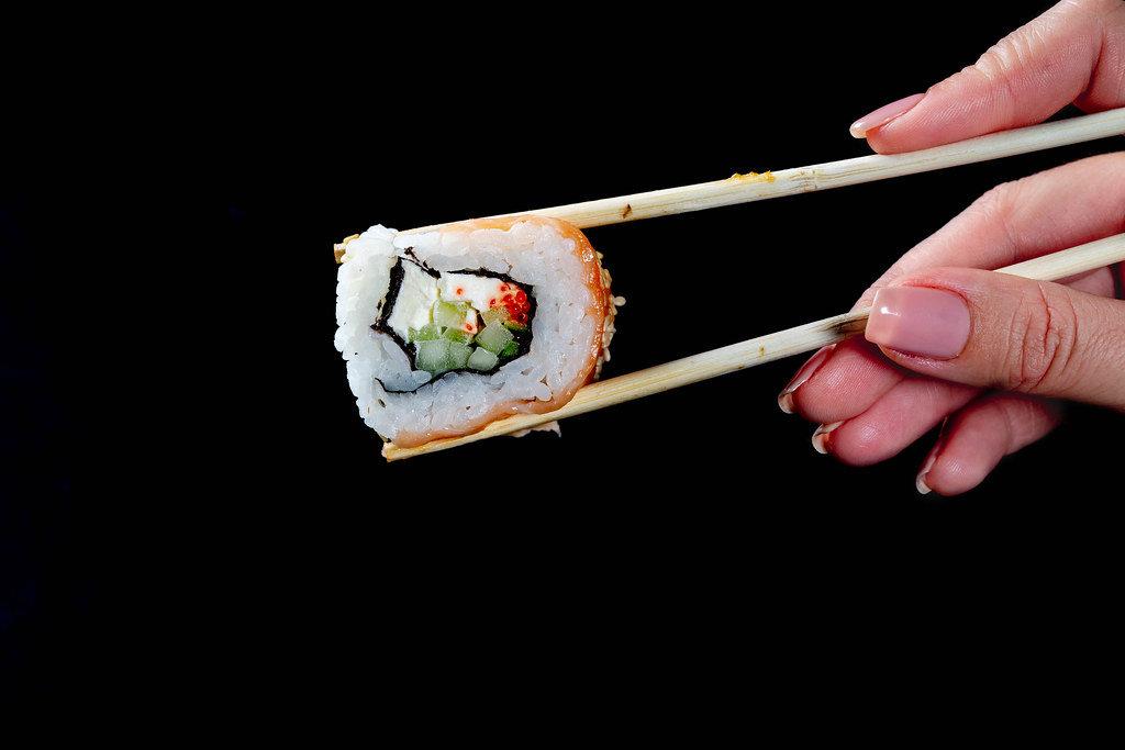 California Sushi roll keeps in chopsticks girl