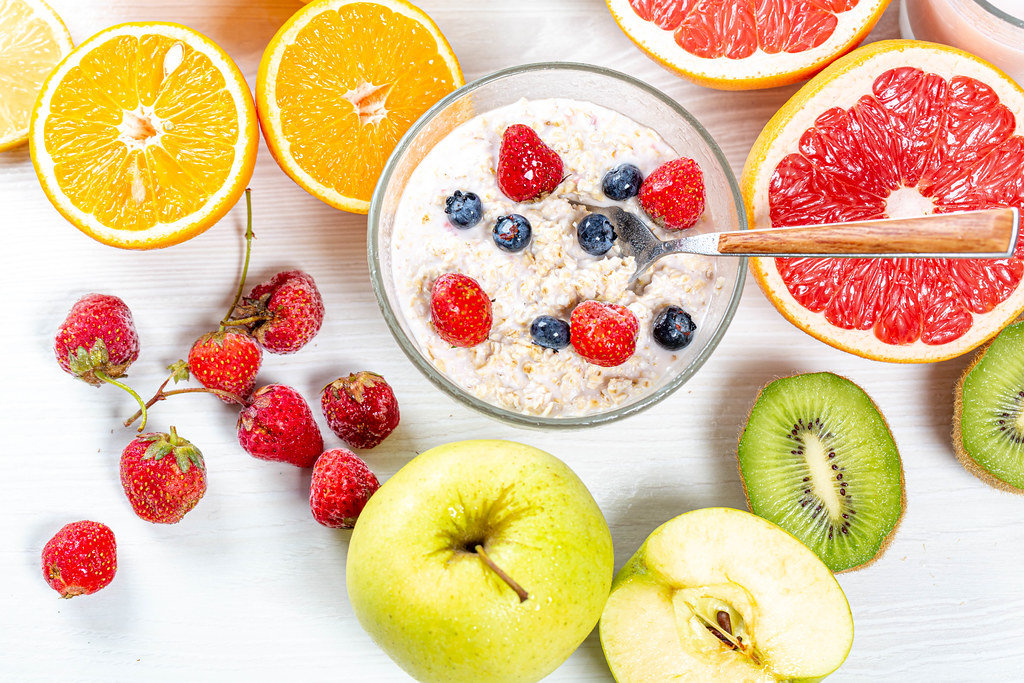 Top view, bowl of oatmeal with milk and lots of colorful fruits and berries
