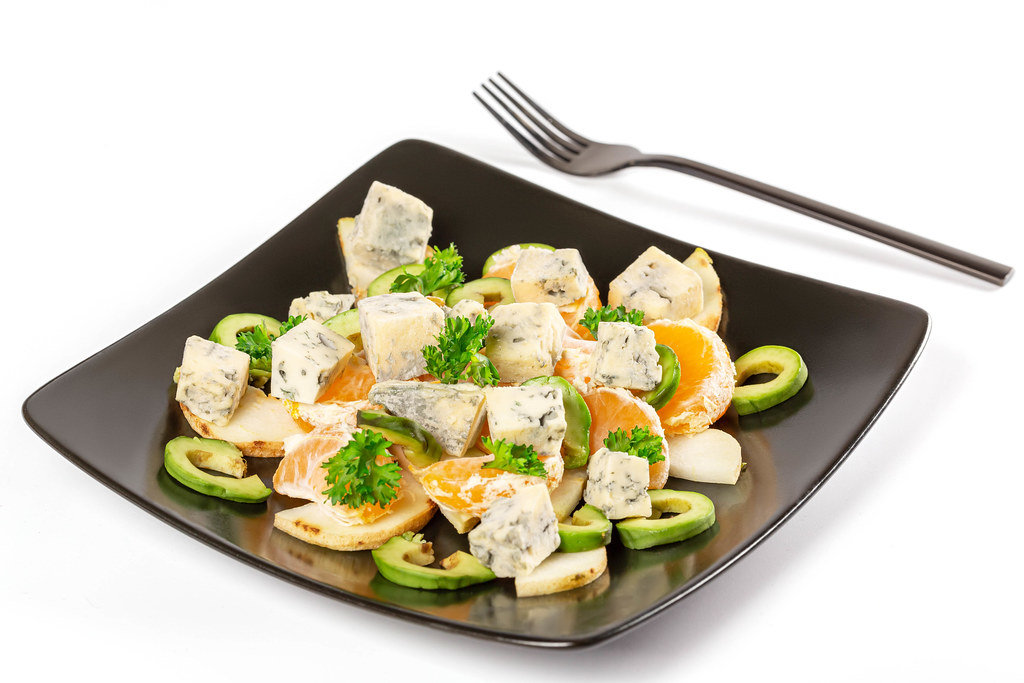 Salad with fruit and dor blue cheese on a black plate
