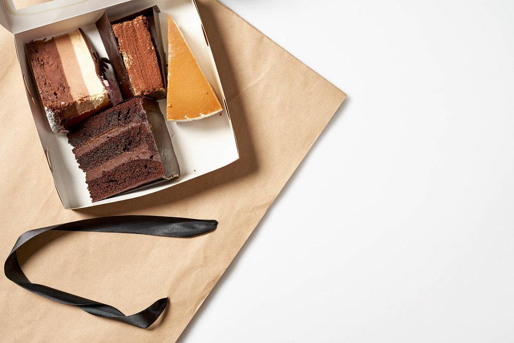 Aufnahme von oben: eine offene Box mit vier verschiedenen Tortenstücken auf einer Papiertüte