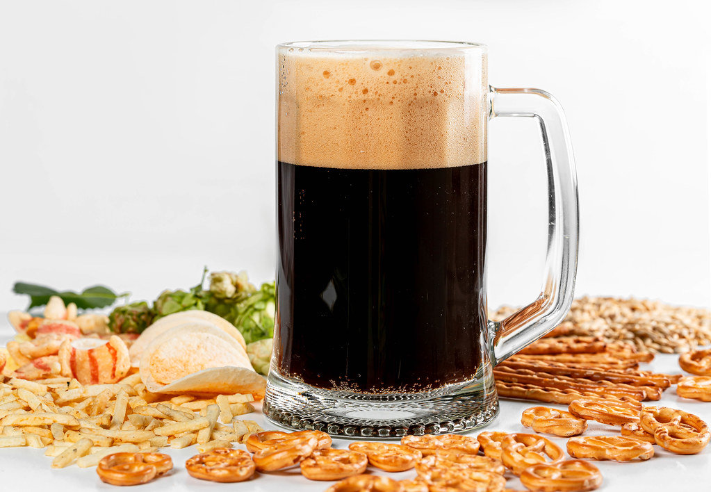 Set of different snacks on a white background with a glass of fresh beer