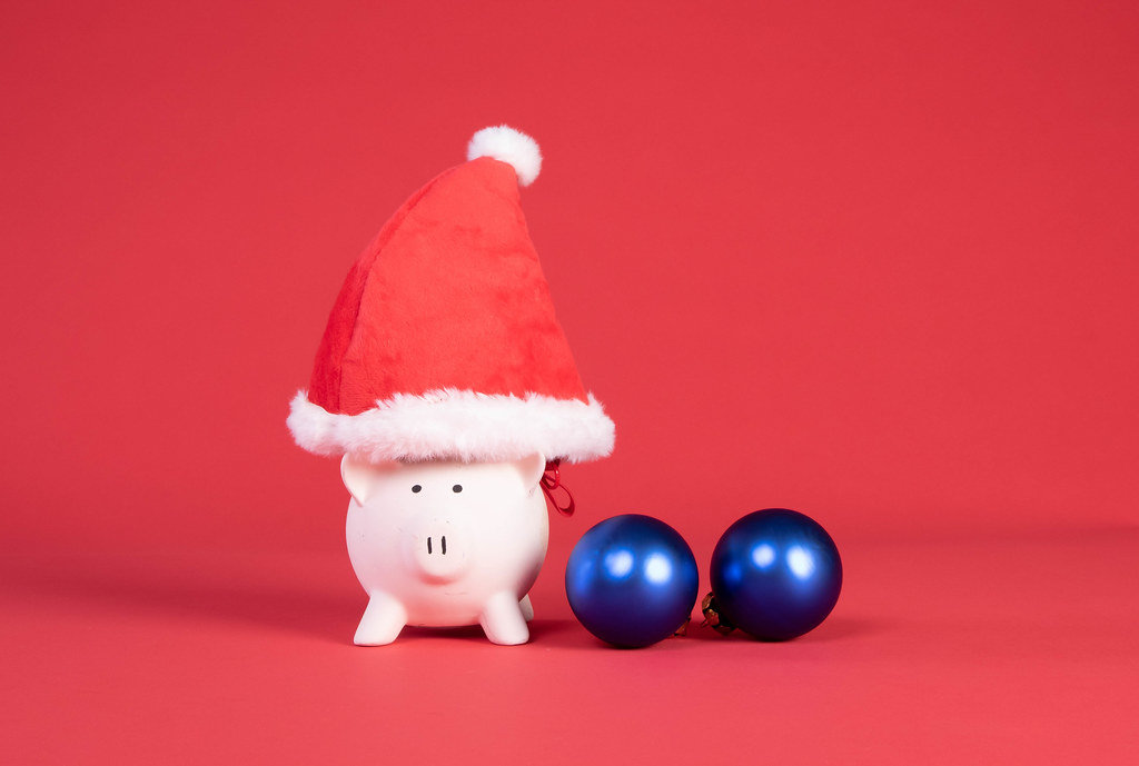 Piggy bank with Christmas hat and ornaments on red background