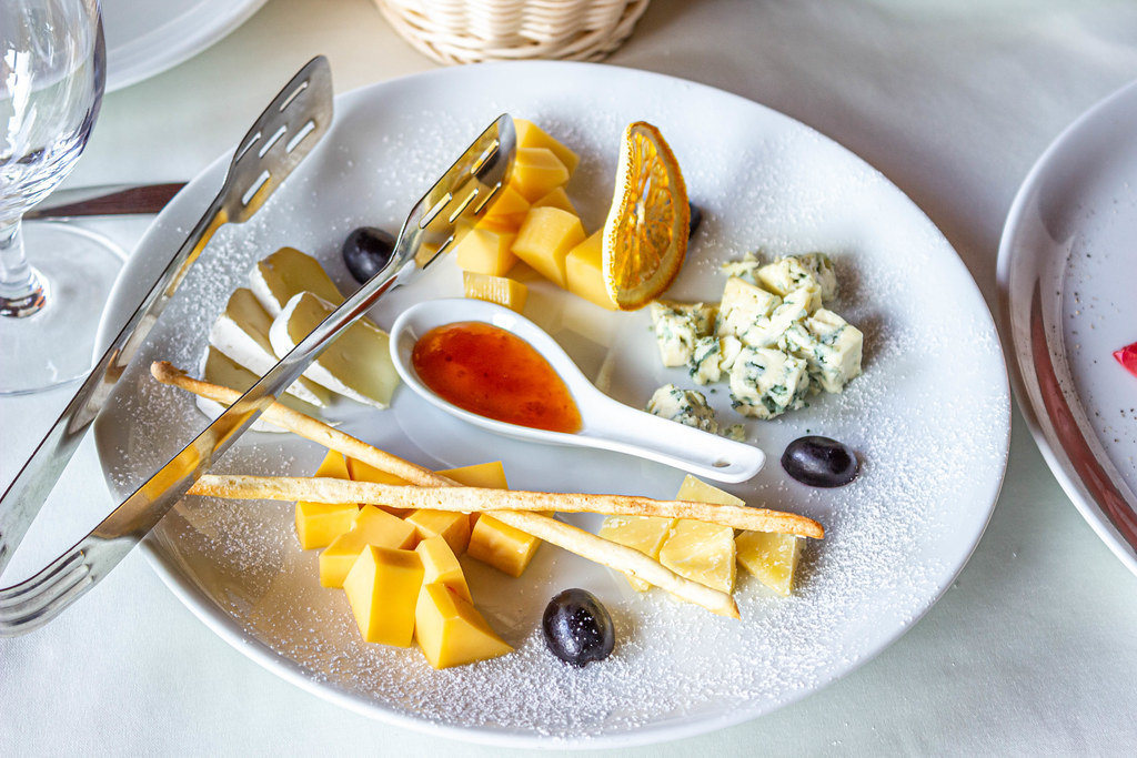 Cheese plate: hard cheese, Camembert cheese, Dor blue, bread sticks, honey and grapes on plate