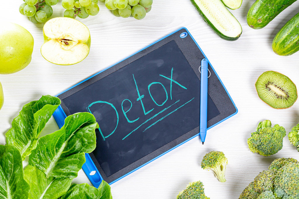 The concept of Detox. Fresh green fruits and vegetables on white wooden background