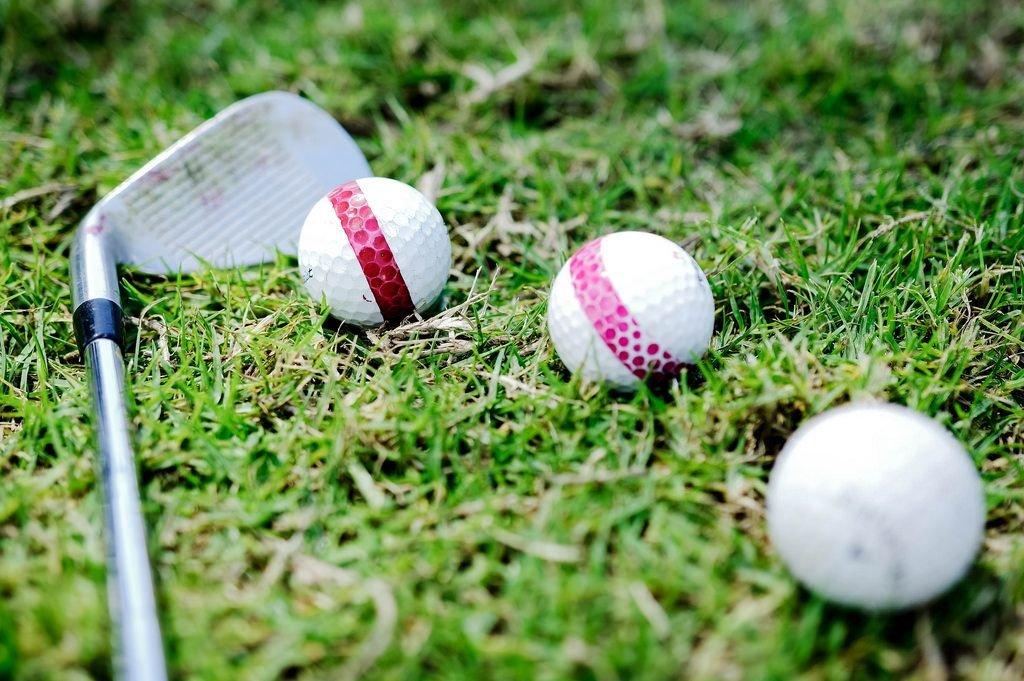 Drei Golfbälle und eine Golfschläger auf dem Grün