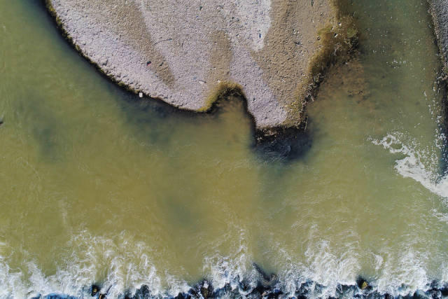 Land and water, Arges river in Romania, aerial view with drone