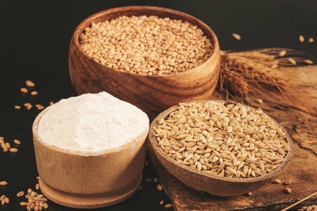 Ripe wheat, barley and flour in wooden bowls