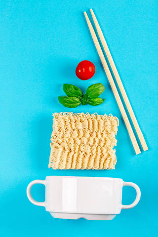 White tureen on a blue background with ingredients for a quick lunch. Raw instant noodles