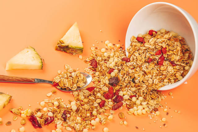 Scattered oatmeal with berries, seeds and pineapple pieces on an orange background