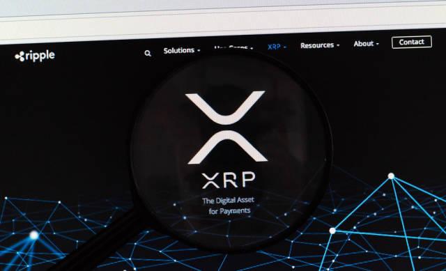 Ripple-Logo am PC-Monitor, durch eine Lupe fotografiert