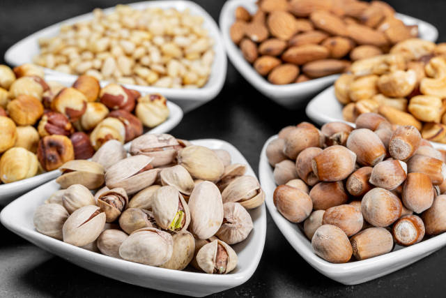 Set of different nuts in white bowls on a black background