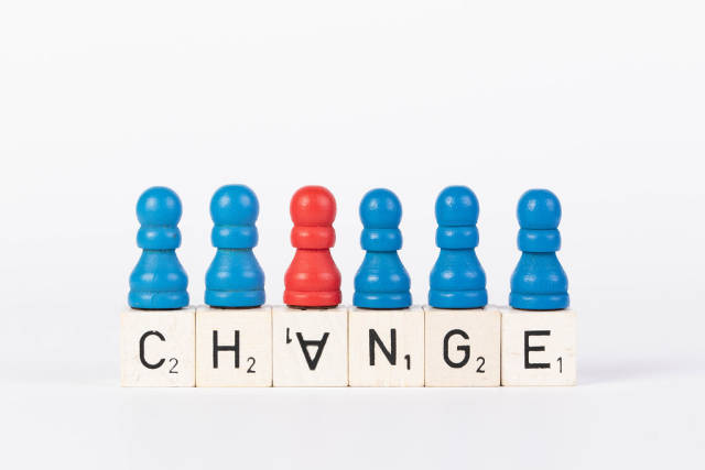 Word Change written on wooden blocks with pawns in various colors on white background