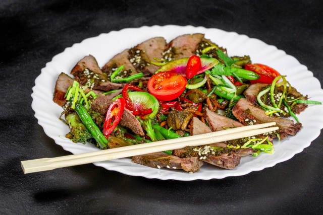 Baked vegetables and beef with chopsticks