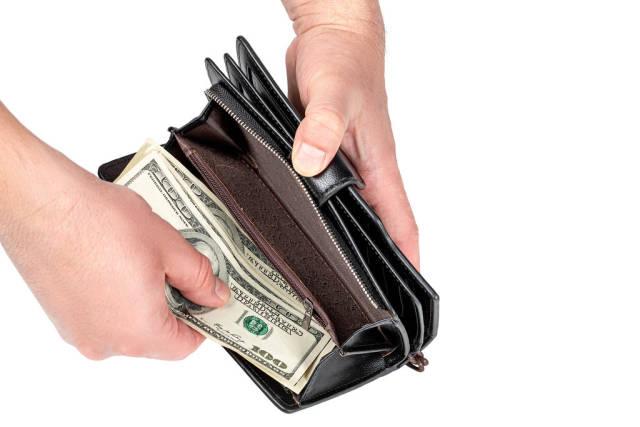 Mens hands put money in the wallet