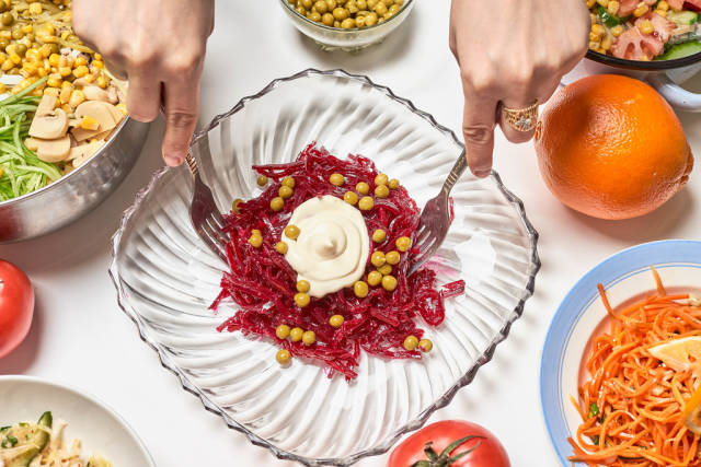 Woman mixing korean beet salad with mayonnaise