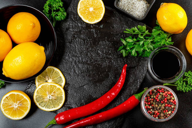 Spices and lemons on a dark background, top view