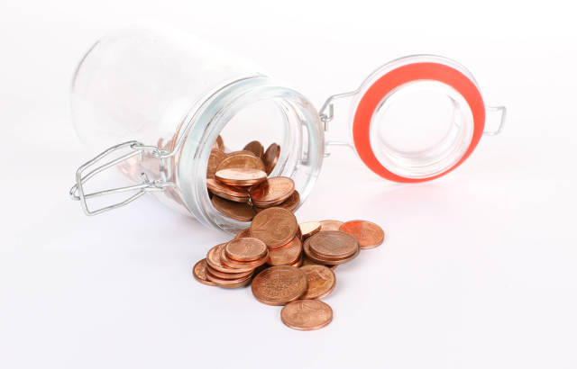 Euro cent coins spilling out of a jar on white background