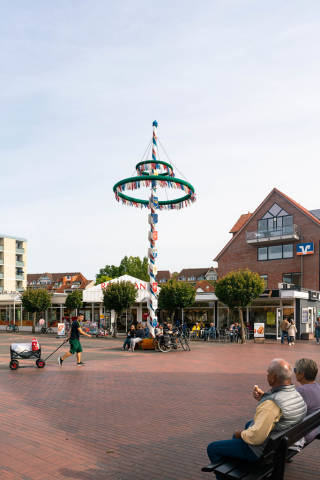 Monument of the Mast decorated with different flags in the city-center  of German resort town