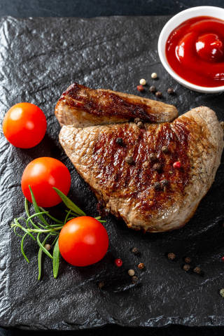 Delicious veal steak with tomatoes and spices on a black stone tray
