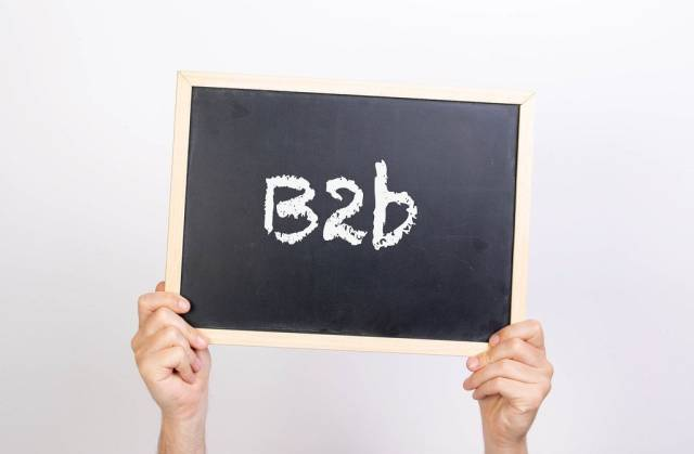Hands holding blackboard with text B2b