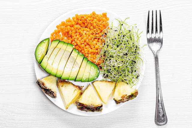 Lentils with micro-green onions, fresh pieces of avocado and pineapple. Top view