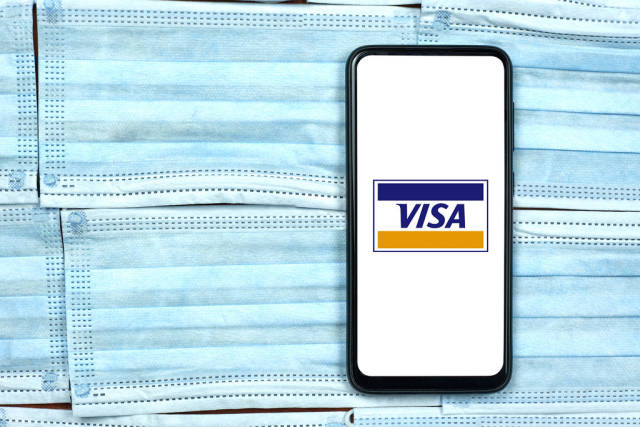 Visa company logo on smartphone screen over the face masks. Global company during coronavirus crisis