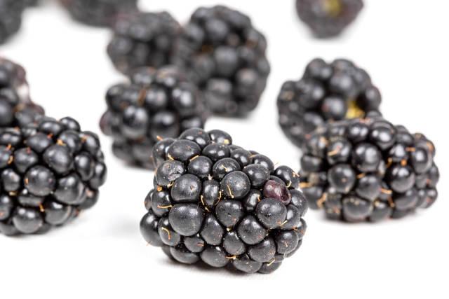Black berries of ripe blackberries on a white background
