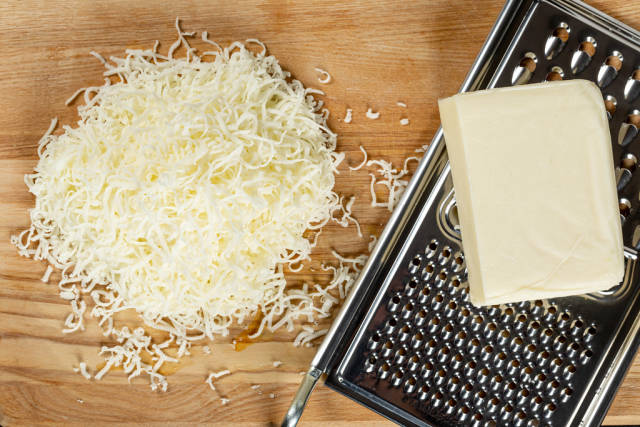 Grated mozzarella cheese, slab of cheese and metal cheese grater, top view