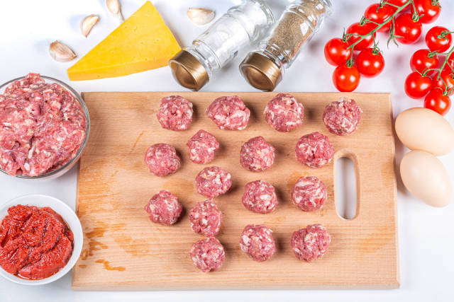 Raw meat balls with sauce ingredients on the table, top view