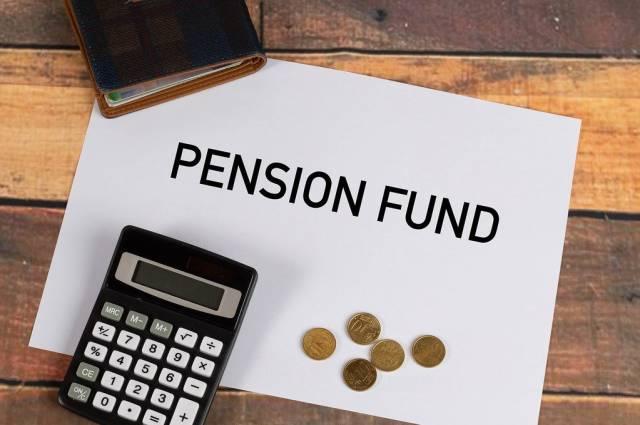 """Pensionsfond""""  auf Papier geschrieben, neben einem Taschenrechner, Kleingeld und einer Geldbörse"""