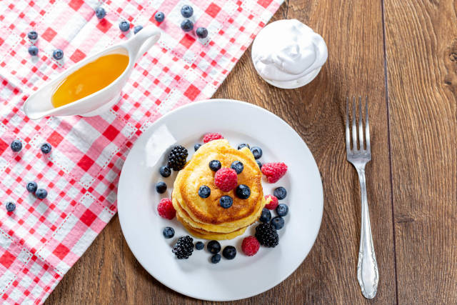 The view from the top the pancakes with fresh berries, honey, and cream with a fork. The concept of Breakfast