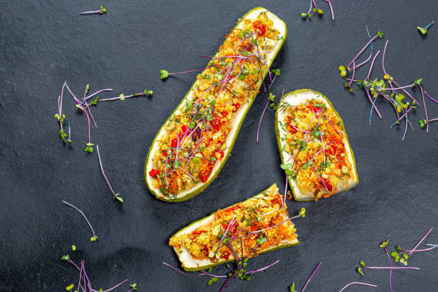 Top view of baked zucchini with vegetables and couscous on a black background with fresh micro-greens of cabbage