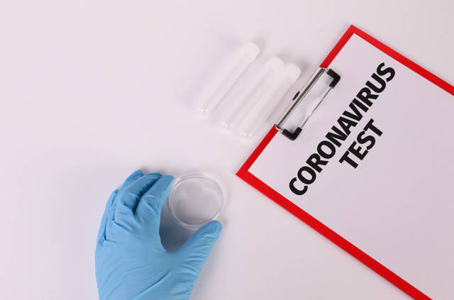 Hand in blue medical glove holding empty test tube and clipboard with Coronavirus test text
