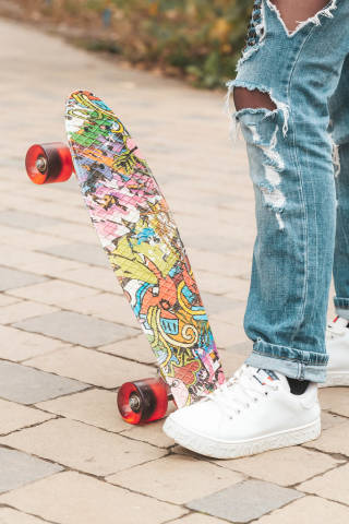 Skateboard and girl legs in city park