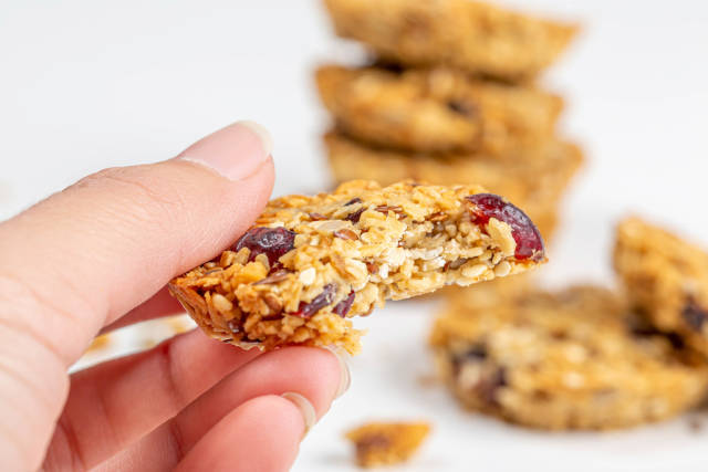 Close-up, a piece of oatmeal cookies with seeds and raisins in a womans hand