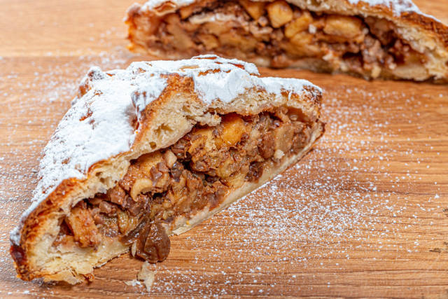 Homemade apple strudel with apples, nuts and powdered sugar on wooden background