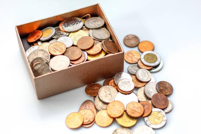 Münzen in einer kleinen Schachtel vor weißem Hintergrund