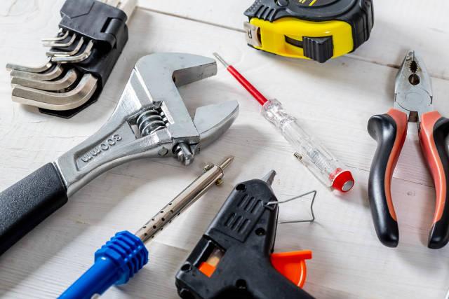 Werkzeuge - Ein Maßband, Imbusschlüssel, Lötkolben, Elektroschraubenzieher, eine Heißklebepistole und ein verstellbarer Schraubenschlüssel