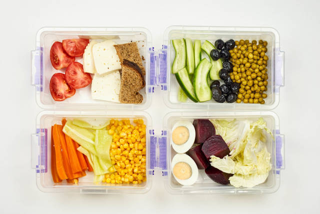 Set of vegetarian food packed in the lunchbox for four persons