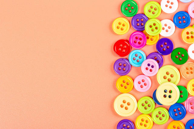 Top view of multicolored buttons on orange background