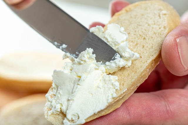 Close-up of hand spread cheese on bread with a knife