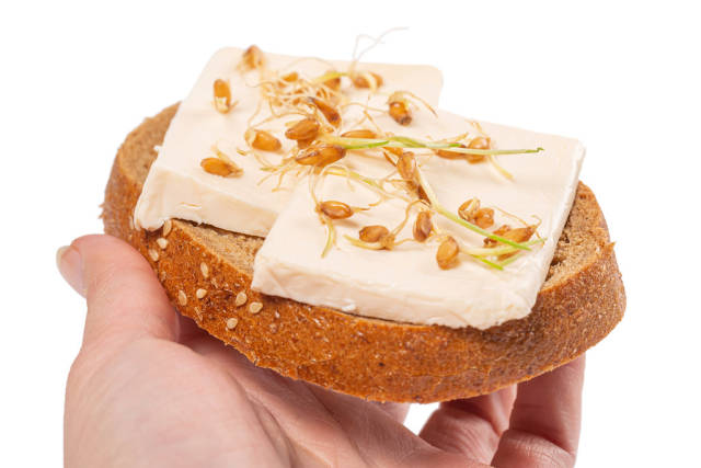 Sandwich with cheese and sprouted wheat in a womans hand