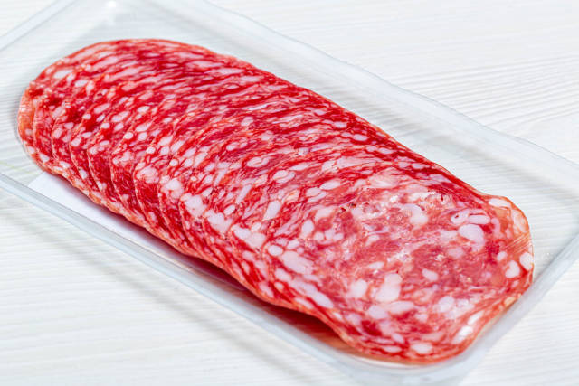 Smoked salami sausages slices on white background