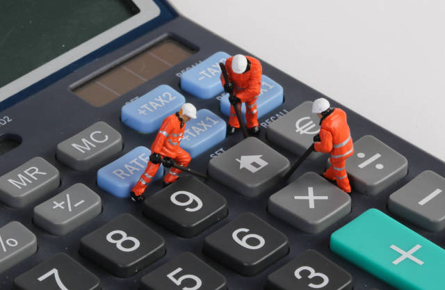 Miniature technician repairing home button on calculator