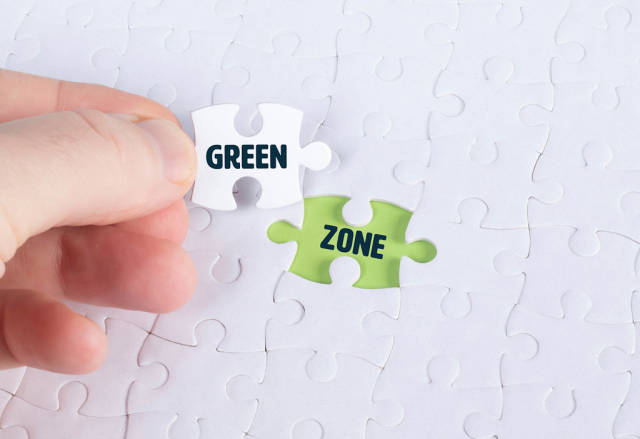 Hand holding piece of jigsaw puzzle with word green & zone