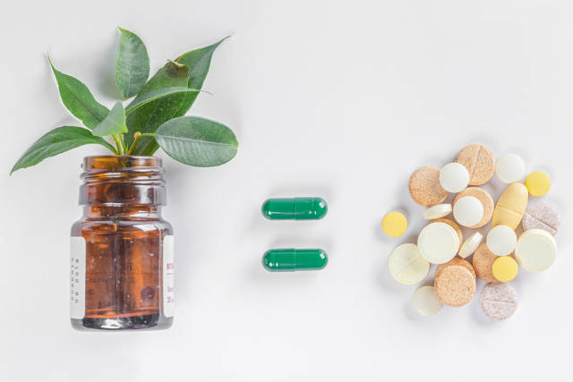 Medical drugs concept, bottle with green leaves and heap of pills