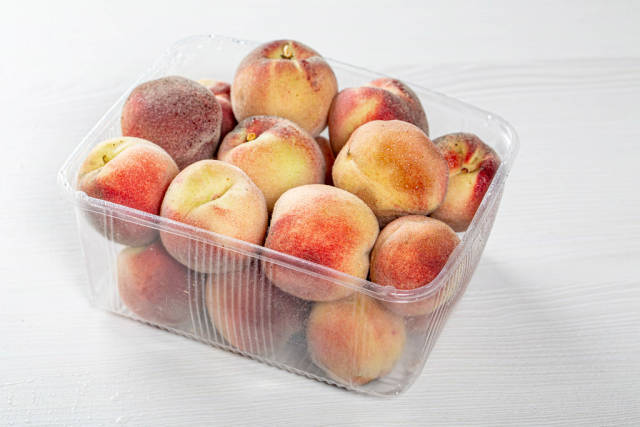 Ripe peaches in a plastic container